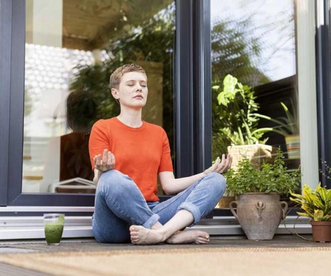 Frau meditiert auf der Terasse