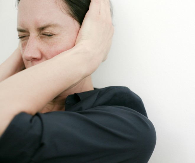 Foto Frau hält sich die Ohren zu